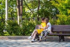 Filles avec des téléphones dans leurs bras embrassant se reposer en parc sur un banc Photos libres de droits