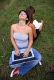 Filles avec l'ordinateur portatif et le livre Photographie stock libre de droits