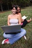 Filles avec l'ordinateur portatif et le livre Photos stock