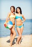 Filles avec la boule sur la plage Photo stock