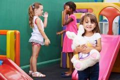 Filles avec la peluche dans le jardin d'enfants Image stock
