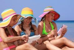 Filles avec le comprimé sur la plage Photos stock
