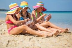 Filles avec le comprimé sur la plage Photographie stock libre de droits