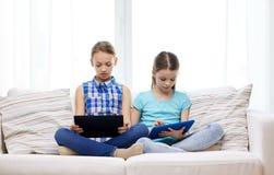 Filles avec le PC de comprimé se reposant sur le sofa à la maison Photos libres de droits