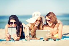 Filles avec le PC de comprimé sur la plage Photo stock