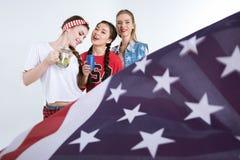Filles avec les boissons potables de drapeau américain d'isolement sur le blanc Photo libre de droits
