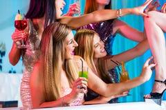 Filles avec les cocktails de fantaisie dans le club de striptease Images stock
