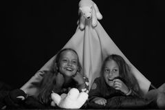Filles avec les visages heureux regardant la TV Les enfants portant les jammies rouges regardent la TV parmi les jouets mous Photo stock