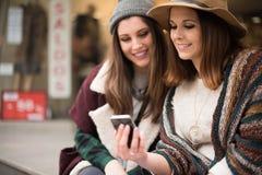 Filles avec un smartphone dans la ville Image libre de droits