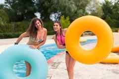 Filles ayant l'amusement au parc aquatique avec le flotteur en caoutchouc Photos stock