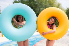 Filles ayant l'amusement au parc aquatique avec le flotteur en caoutchouc Image libre de droits
