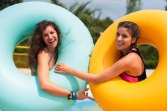 Filles ayant l'amusement au parc aquatique avec le flotteur en caoutchouc Images stock