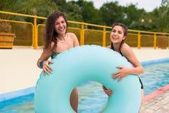 Filles ayant l'amusement au parc aquatique avec le flotteur en caoutchouc Photographie stock libre de droits
