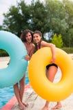 Filles ayant l'amusement au parc aquatique avec le flotteur en caoutchouc Photos libres de droits