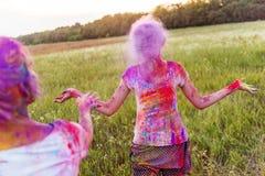 Filles ayant l'amusement et jetant la poudre colorée au festival de holi Image stock