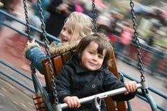 Filles ayant l'amusement sur le carrousel Photo libre de droits