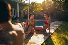 Filles ayant la réception au bord de la piscine Photo stock