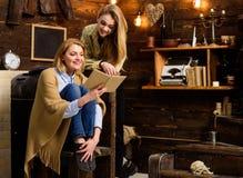 Filles blondes avec des sourires lumineux lisant ensemble Femme enveloppée dans le livre se tenant couvrant de laine Mère et fill Image libre de droits