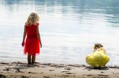 Filles blondes dans la robe rouge et la robe jaune à la mèche de rivière Images libres de droits