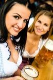 Filles buvant de la bière chez Oktoberfest Photographie stock libre de droits