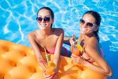 Filles buvant des cocktails dans la piscine Photos stock