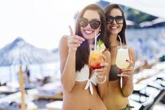 Filles buvant des cocktails sur la plage Image stock