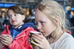 Filles buvant du café chaud dans l'aéroport Photographie stock libre de droits