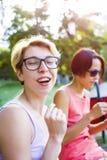 Filles buvant du café en parc Image stock