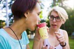 Filles buvant du café en parc Image libre de droits
