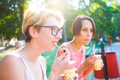 Filles buvant du café en parc Photographie stock libre de droits