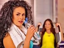 Filles buvant l'eau de bouteille dans le gymnase de sport Photographie stock