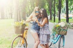 Filles chics de boho heureux avec le mobile sur des bicyclettes en parc Images stock