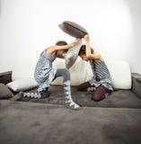 Filles combattant avec des coussins sur le divan image stock
