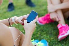 Filles courantes ayant l'amusement dans le parc avec le téléphone portable Photographie stock libre de droits