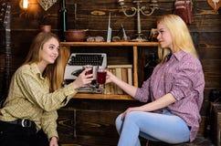 Filles détendant et buvant du vin chaud Amis dans des équipements occasionnels ayant l'amusement tout en célébrant avec du vin, e Photographie stock libre de droits