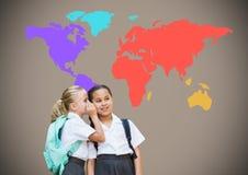 Filles d'école chuchotant devant la carte colorée du monde Photos stock