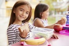 Filles d'école primaire mangeant à la table de repas scolaire photographie stock libre de droits