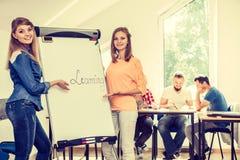 Filles d'étudiant écrivant apprenant le mot sur le tableau blanc Photo stock