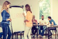 Filles d'étudiant écrivant apprenant le mot sur le tableau blanc Image libre de droits
