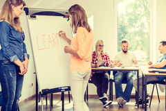 Filles d'étudiant écrivant apprenant le mot sur le tableau blanc Photos stock