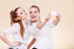 Filles d'étudiant d'amis prenant la photo d'individu avec le téléphone intelligent Photos stock