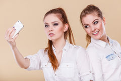 Filles d'étudiant d'amis prenant la photo d'individu avec le téléphone intelligent Photographie stock