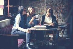 Filles d'étudiants ayant l'amusement en café Image stock