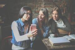Filles d'étudiants ayant la conversation et à l'aide du téléphone intelligent Image stock