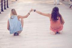 Filles d'ados d'été s'asseyant sur des planches à roulettes Images libres de droits