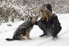 Filles d'amitié et un chien dans la neige Photos libres de droits