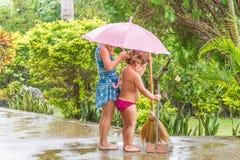 Filles d'enfant nettoyant le chemin, dehors, pendant la pluie Photo libre de droits