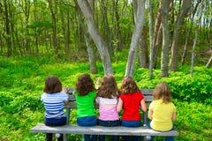 Filles d'enfants s'asseyant sur le banc de parc regardant la forêt Photos libres de droits