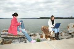 Filles d'université à l'extérieur avec l'ordinateur portatif Image libre de droits