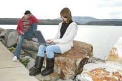 Filles d'université à l'extérieur avec l'ordinateur portatif Photographie stock libre de droits